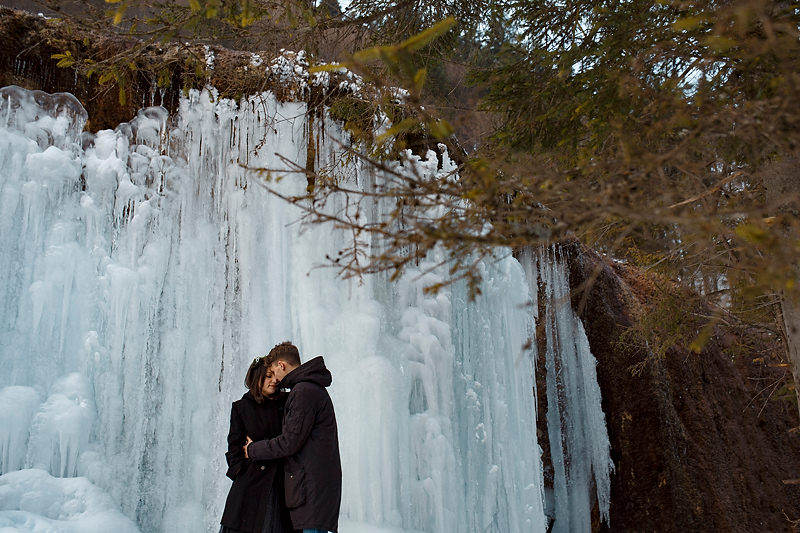 Imbratisarea unui cuplu in fata unei cascade inhetate