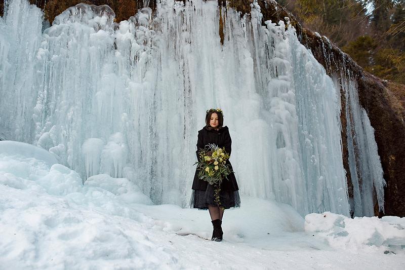Fata care tine un buchet de flori in fata unei cascade inghetate