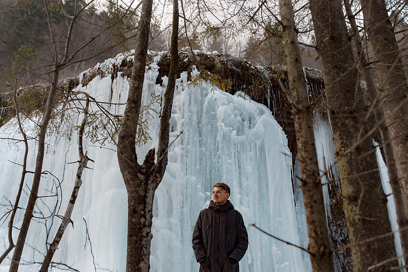 Adolescent in fata unei cascade inghetate