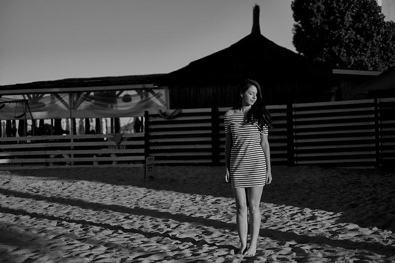 Fotografie al-negru cu adolescenta in soare imbracata intr-o rochita dungata