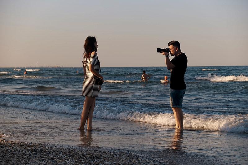 Videorgraf filmand o tanara pe plaja