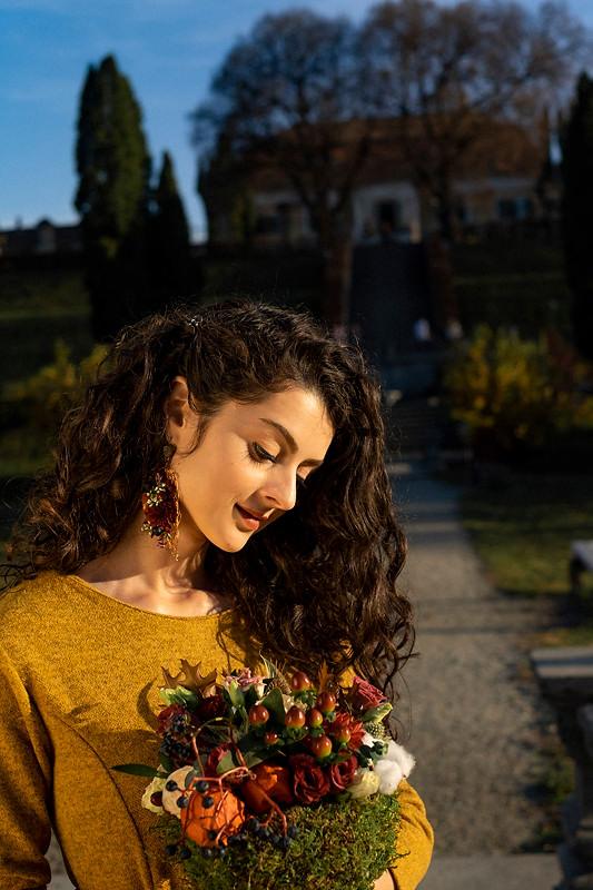 Portretul fetei este din profil si tine in maini un buchet de flori naturale