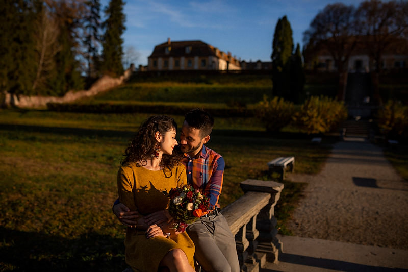 Cuplu sezand in fata la Palatul Brukenthal asaturi de un buchet
