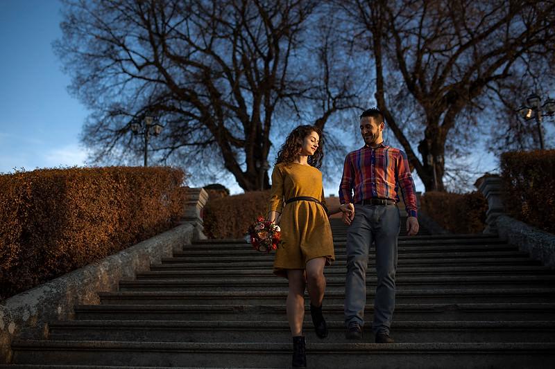Cuplu coborand scarile iar in fundal se ved teii de la Palatul Brukenthal