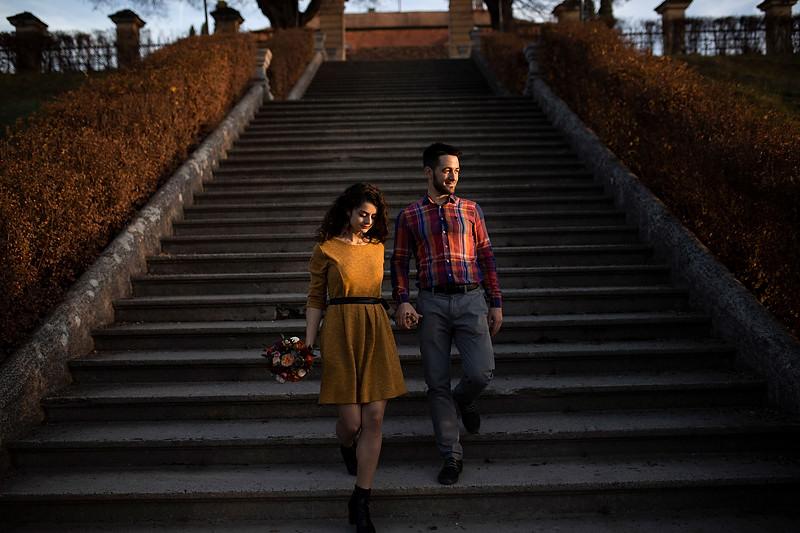 Cuplu cobarand scarile, iubita coboara cu un pas mai in fata decat iubitul ei