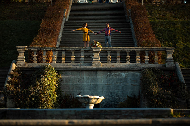 Pe scarile promenadei se vede un cuplu tinandu-se de mana