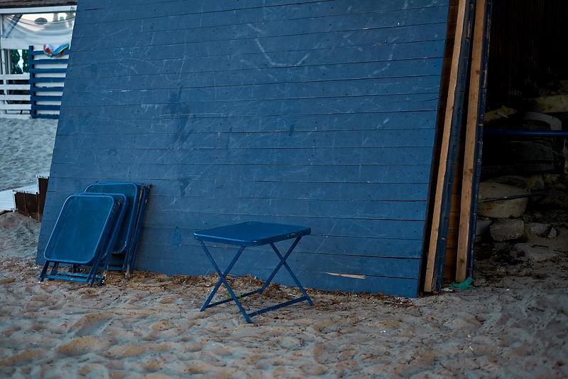 Un panou si un scaun albastru pe plaja
