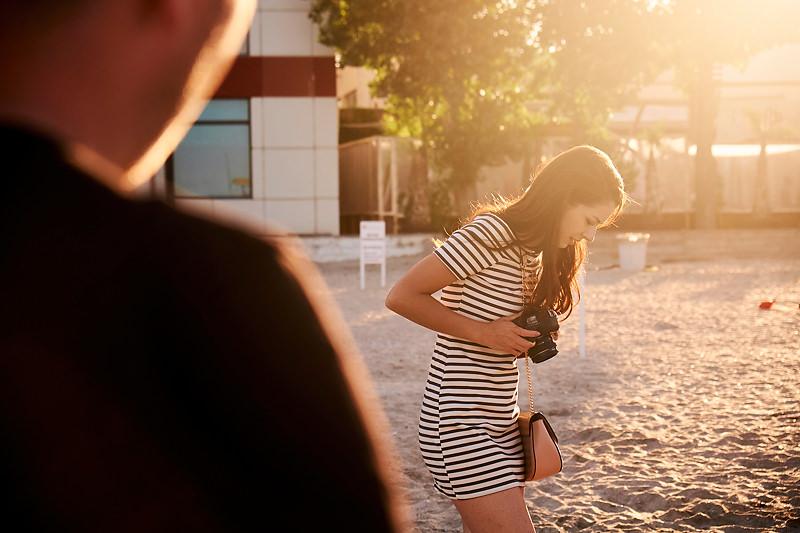 Adolescenta cu un aparat foto in mana pe plaja