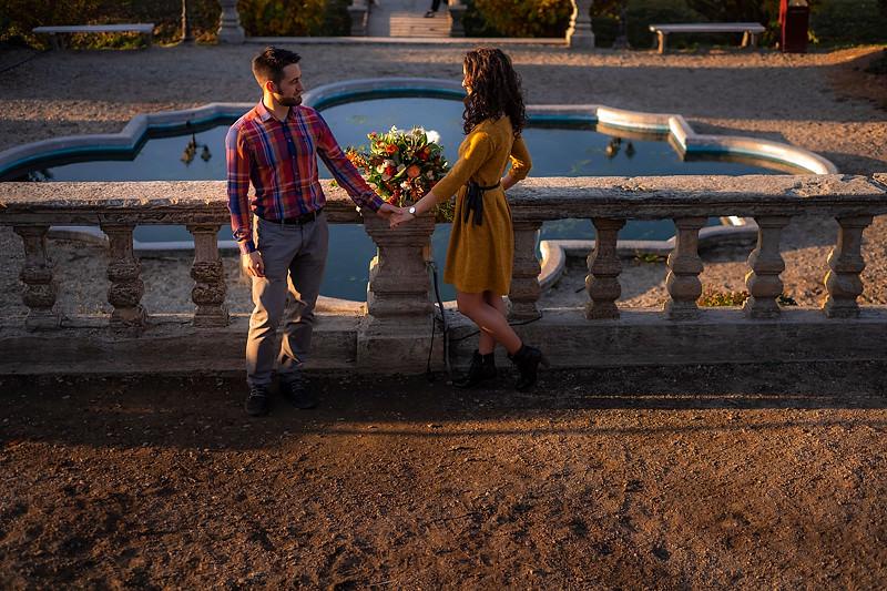 Fotografie romantica cu un cuplu care sta alturi de funtana arteziana din gradina Palatul Brukenthal din Avrig