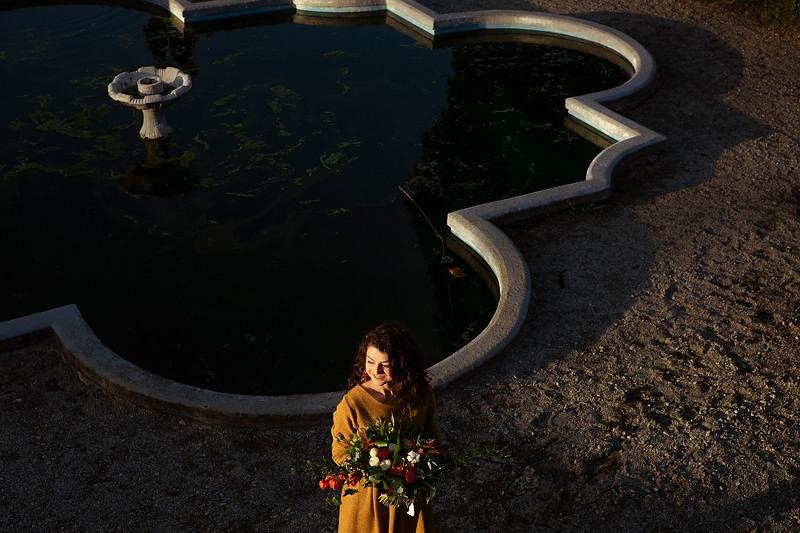 Un buchet de mireasa realizat de Contessina Events este tinunt de o fata care pozeaza in gradina de la Palatul Brukenthal din Avrig