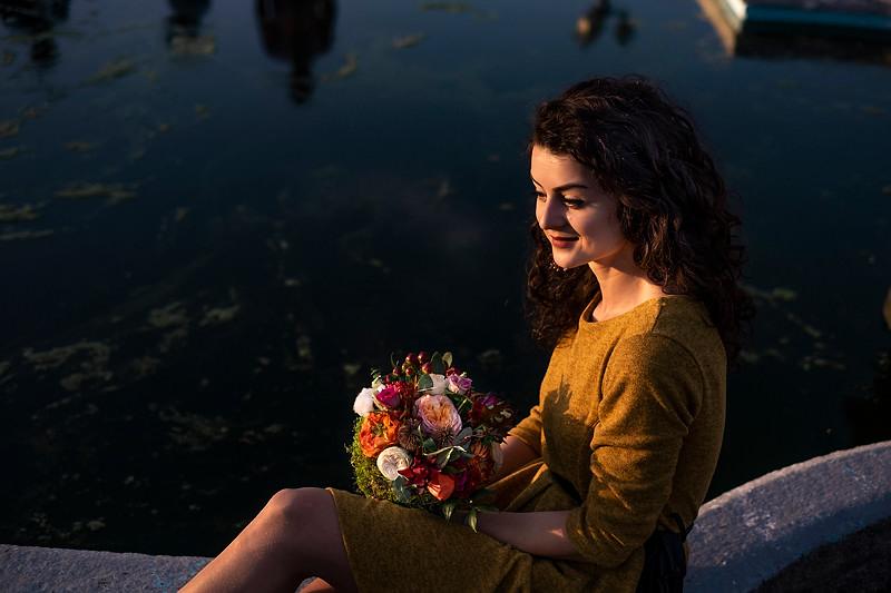 Un buchet de mireasa in mainile unei viitoare mirese. fata admira buchetul minunat realizat de Contessina Events