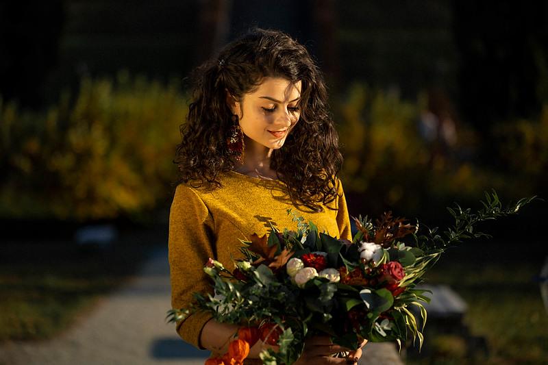 Fata carliontata se uita la buchetul de flori iar expresia arata incantare
