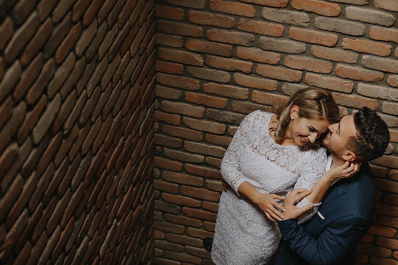 cuplu imbratisandu-se alaturi de un perete de caramida