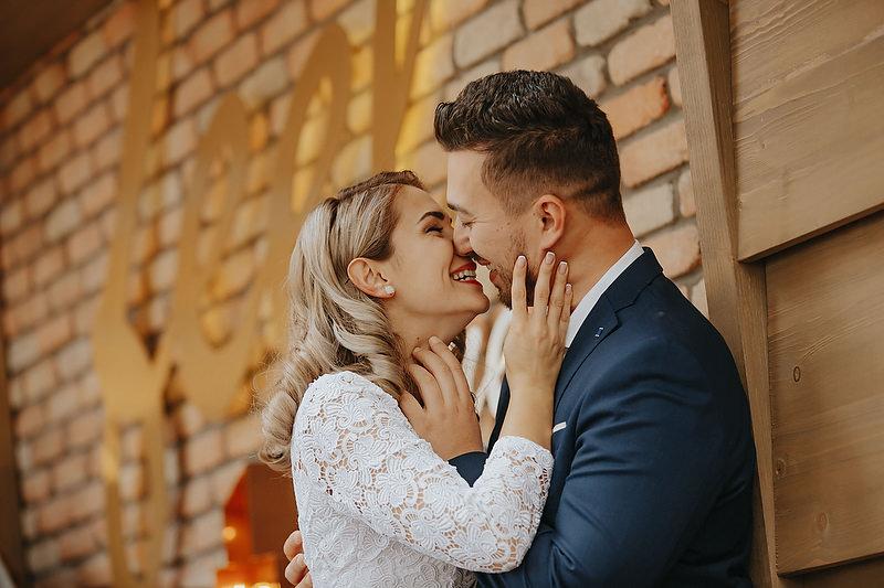 Sarutul unui cuplu imbracat festiv
