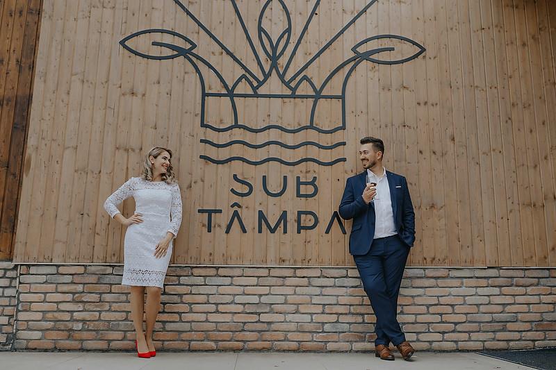 Cuplu imbracat festiv dupa cununie rezemati pe un perete cu lambriu de lemn